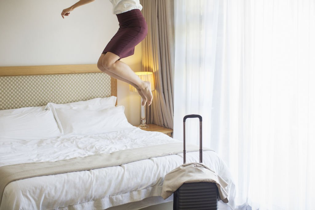 Businesswoman Jumpin on Bed in Hotel Room